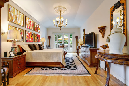Luxury large master bedroom interior with antique carved wooden furniture, king size bed, vintage chandelier and hardwood floor. Northwest, USA