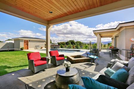 porche arrière traditionnel avec terrasse et une extension de toit. arrangement de sièges confortables, d'un foyer et une piscine à l'arrière. Northwest, États-Unis Banque d'images