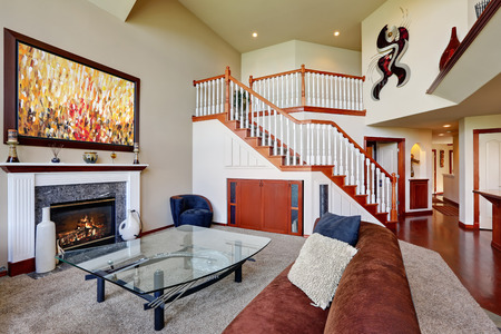 the vaulted: American living room with high vaulted ceiling and staircase. Brown corner couch, designed cocktail table and fireplace. Northwest, USA