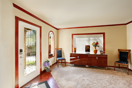 Entrance room with comfortable sitting area. Large console table with two chairs, arched window, carpet floor and view  of glass stained front door. Northwest, USA