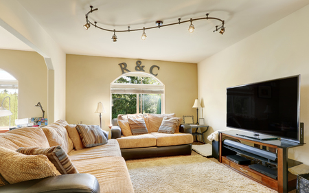 Cozy family room furnished with leather sofas with beige cushions. Northwest, USA