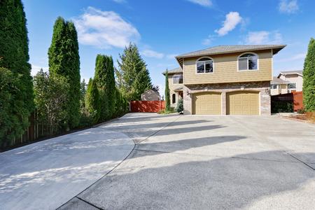 Luxe huis in groene buitenkant verf en grote betonnen oprijlaan, twee garage deuren, baksteen trim. Noordwest, Verenigde Staten Stockfoto - 67380829