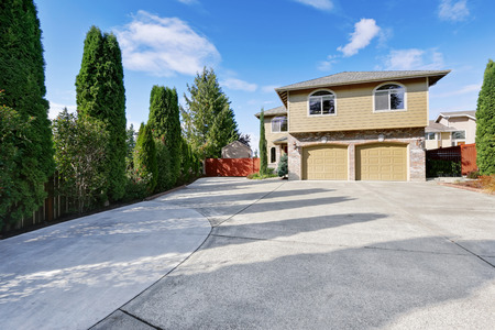 Luxury house in green exterior paint and large concrete driveway, two garage doors, brick trim. Northwest, USA