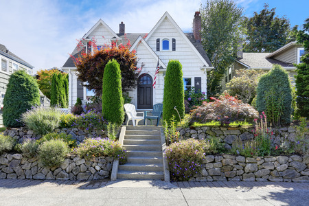 American craftsman style home with beautiful landscape design, trimmed shrubs, rocks and flowers. Northwest, USA