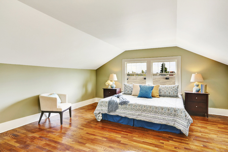 Spacious upstairs bedroom with vaulted ceiling, green walls and hardwood floor. Northwest, USA