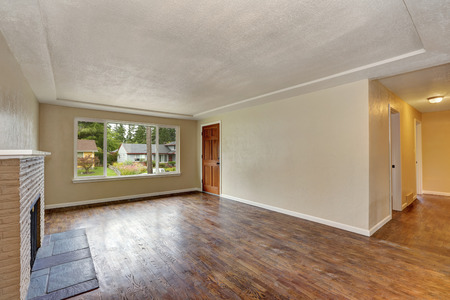 Unfurnished beige living room interior in empty house with fireplace and dark brown hardwood floor. Northwest, USA