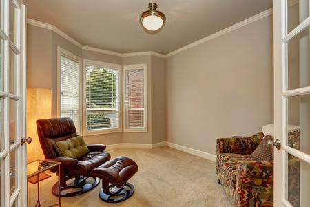 Cozy sitting room interior with leather armchair, carpet floor and beige walls. Northwest, USA 版權商用圖片