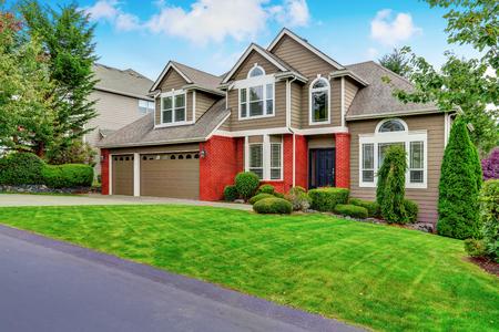 Mooie gevelbekleding van beige huis met rode baksteenversiering en keurig getrimde voortuin. Northwest, VS. Stockfoto