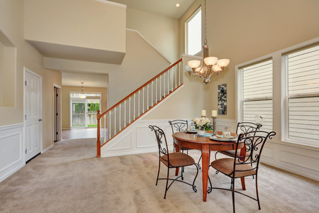 elegant staircase: Beige dining room interior with high ceiling and staircase. Elegant table setting and wrought iron chairs. Northwest, USA
