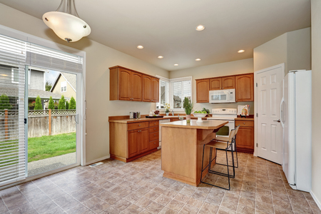 tile flooring: Classic style kitchen interior with tile flooring, white appliances, wooden storage combination, kitchen island and pantry. Glass doors lead out to the back yard. Northwest, USA Stock Photo