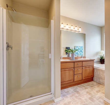 Bathroom interior with glass door shower, bath tub view and small double sink vanity cabinet with a mirror. Northwest, USA