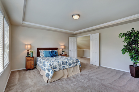 Spacious bedroom with queen size bed, floral patterned bedding with nice blue pillows and carpet floor. Opened double doors to the hallway. Northwest, USA