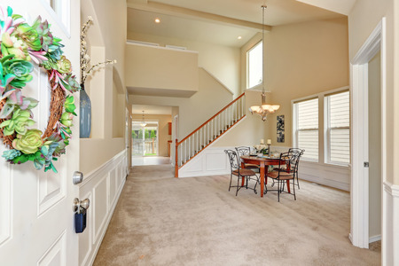 entryway: Opened front door to high ceiling beige dining room interior with carpet floor and staircase. Elegant table setting and wrought iron chairs. Northwest, USA
