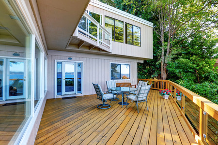 house exterior: Wooden walkout deck with outdoor table set and swinging bench. Modern beige house exterior. Northwest, USA Stock Photo