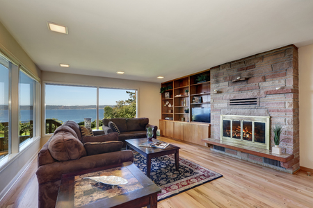 Interior of nicely furnished living room with large windows overlooking water view. Has hardwood floor, brown chocolate sofas, persian style rug, natural stone wall trim and a fireplace. Northwest, USA