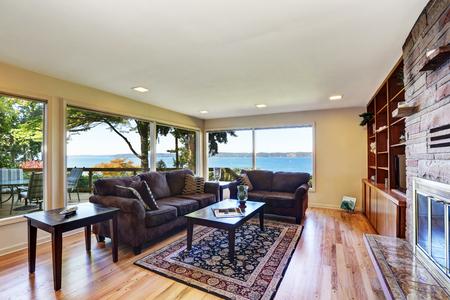 バックデッキを見渡せる大きな窓と素敵な内装のリビング ルームのインテリア。堅木張りの床、茶色のチョコレート ソファ、ペルシャ様式の敷物、