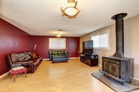 couches: Contrast red wall in the living room with antique fireplace. Has light brown tones hardwood floor and two leather couches. Northwest, USA