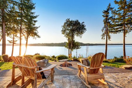 adirondack: Back yard of waterfront house with adirondack chairs and fire pit.  Beautiful water view at sunset. Northwest, USA