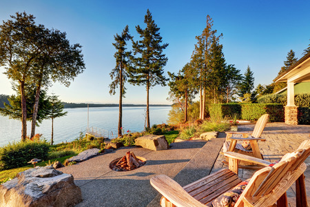 fire pit: Back yard of waterfront house with adirondack chairs and fire pit.  Beautiful water view at sunset. Northwest, USA