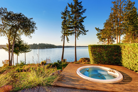 Exterior of waterfront house with jacuzzi at the back yard and perfect water view. Northwest, USA