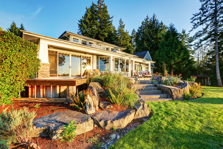 Back yard of waterfront house at sunset. Perfect Natural stone landscape design. Northwest, USA