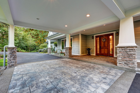 white trim: View of driveway with an all weather covered entry. White columns with natural stone trim. Northwest, USA Stock Photo