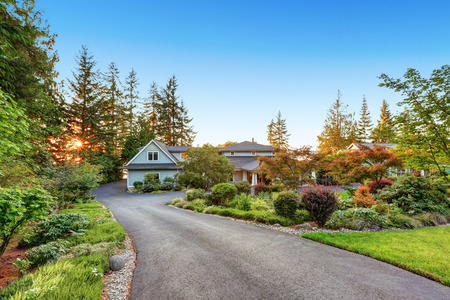 custom built: Custom built luxury house with long concrete driveway and perfect landscape design. Northwest, USA Stock Photo