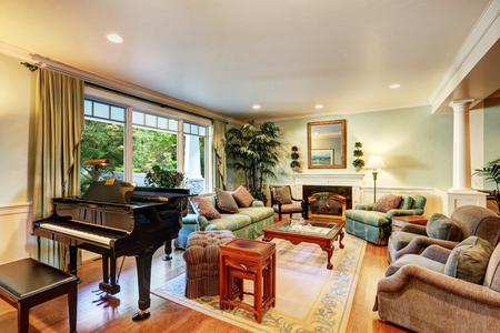 classic living room: Cozy American classic living room interior design with piano and comfortable green sofa set. Northwest, USA Stock Photo