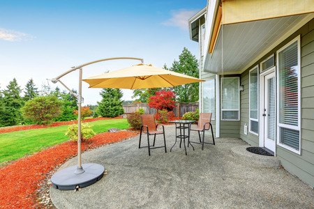 house windows: Concrete floor patio area with table, chairs and opened umbrella. Northwest, USA