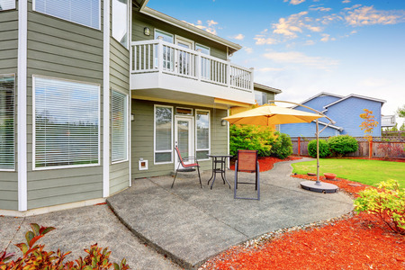 garden styles: Concrete floor patio area with table, chairs and opened umbrella. House exterior. Northwest, USA