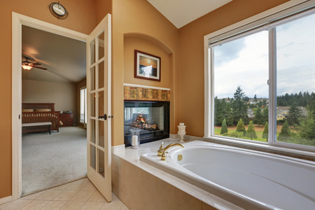 wall mounted: Luxury bathroom interior. Orange brown walls and vaulted ceiling. Wall mounted fireplace with bath tub. Northwest, USA Stock Photo