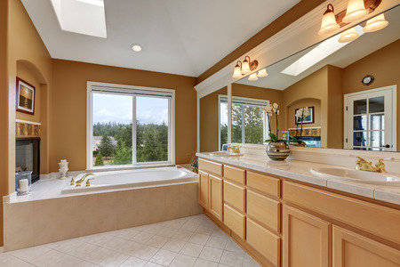 Luxury bathroom interior. Orange brown walls and vaulted ceiling with skylight. Large mirrors and double sink bathroom vanity. Northwest, USA