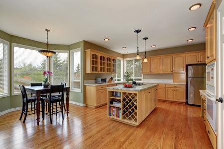 renovated: Maple cabinets and large kitchen island with book shelves and storage units for wine. Kitchen room interior. Dining table set. Northwest, USA