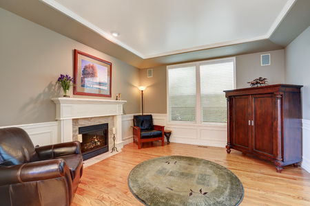 Cozy family room with vintage cabinet and fireplace. Hardwood floor and beige walls. Northwest, USA