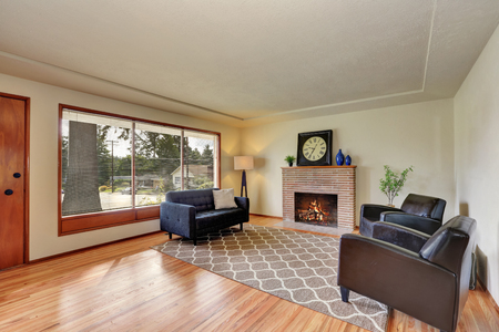 classic living room: Classic living room interior brick trimmed fireplace and polished hardwood floor. Furnished with leather armchairs and gray sofa. Northwest, USA