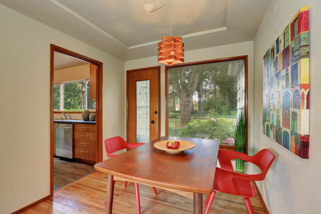 eating area: Dining area interior with red chairs, apples on the table. Has exit to the backyard garden. Northwest, USA