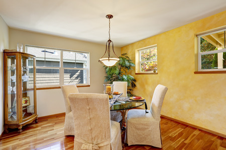 eating area: Interior of dining room with yellow contrast wall and hardwood floor. Elegant chairs, glass cupboard in the corner. Northwest, USA