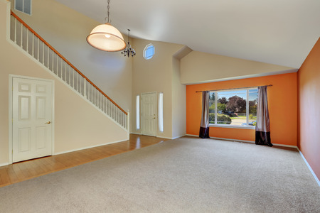 Empty interior of entrance hallway at a new cute, clean house with high vaulted ceiling , freshly painted walls with bright orange accent. Northwest, USA Stock Photo