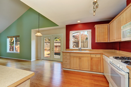 remodeled: Freshly remodeled kitchen room interior with light tones cabinets, white appliances and red contrast wall. Also has glass door to the back yard. Northwest, USA Stock Photo