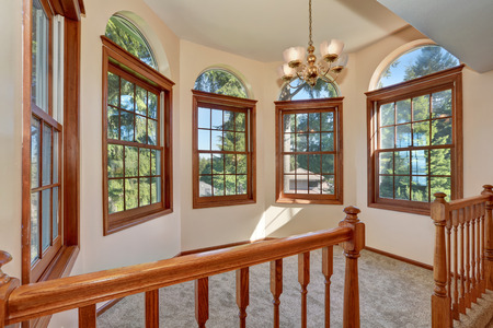 Empty sun room interior with arched windows on the second floor. Northwest, USA