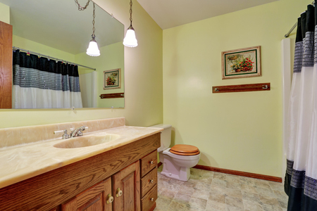 yellow walls: Bathroom vanity with marble counter top and mirror, yellow walls and a toilet. Bathroom interior. Northwest, USA