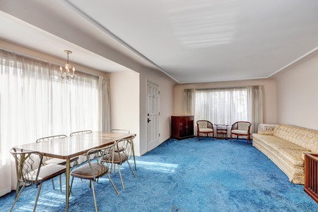 Craftsman style interior. Entrance room connected with dining area. Vintage furniture, dining table for six person and blue soft carpet floor. Northwest, USA Banco de Imagens