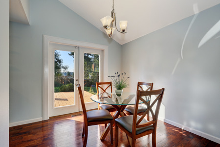 Pastel blue walls and vaulted ceiling of American dining room. Furnished with glass top wooden table and four chairs. Double doors lead out to the back yard. Northwest, USA
