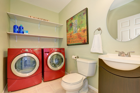 dryer  estate: Interior of laundry room with modern red appliances, toilet and vanity cabinet.  Northwest, USA