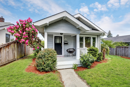 Cute craftsman home exterior with green grass and blooming tree. Northwest, USA