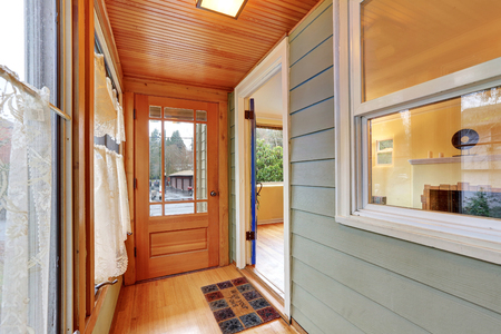 wood paneling: Entrance porch interior with wood paneling, window curtains and doormat. Northwest, USA