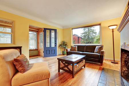 Cozy living room interior with warm yellow walls , fireplace and hardwood floor. Northwest, USA