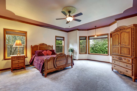 Master bedroom interior with antique hand carved solid wooden  furniture set. Northwest, USA Stock Photo