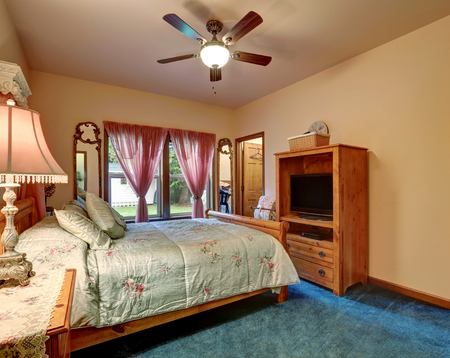 Bedroom interior with walk-in closet, deep blue carpet floor and  ceiling fan. Northwest, USA