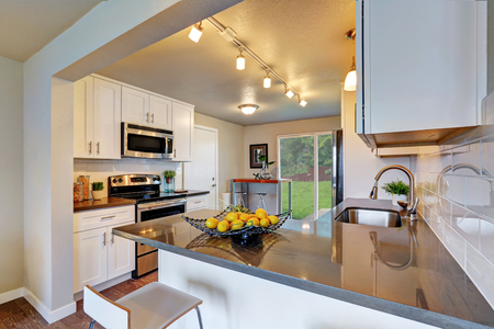 Freshly remodeled kitchen room with white cabinetry and gray counter tops. Northwest, USA Zdjęcie Seryjne - 67386154